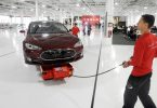 Mark Cuyler, an operations manager at Tesla, walks a Model S through the company's factory in Fremont, California, June 22, 2012. Tesla began delivering the electric sedan to customers on June 22.   REUTERS/Noah Berger   (UNITED STATES - Tags: TRANSPORT SCIENCE TECHNOLOGY BUSINESS) - RTR3417J